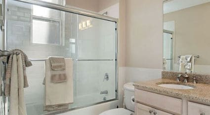 In a framed shower glass enclosure, a rolling shower door provides the convenience of an easy-to-open shower door that is also space-saving.